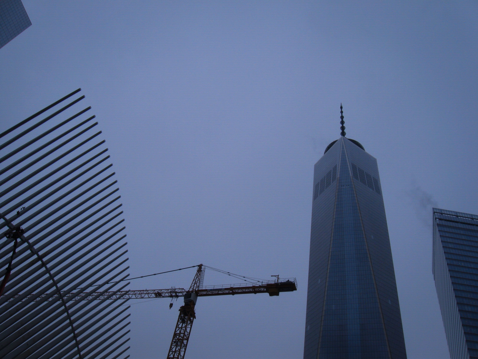 looking up at the top of one world trade center, with a construction crane to the left