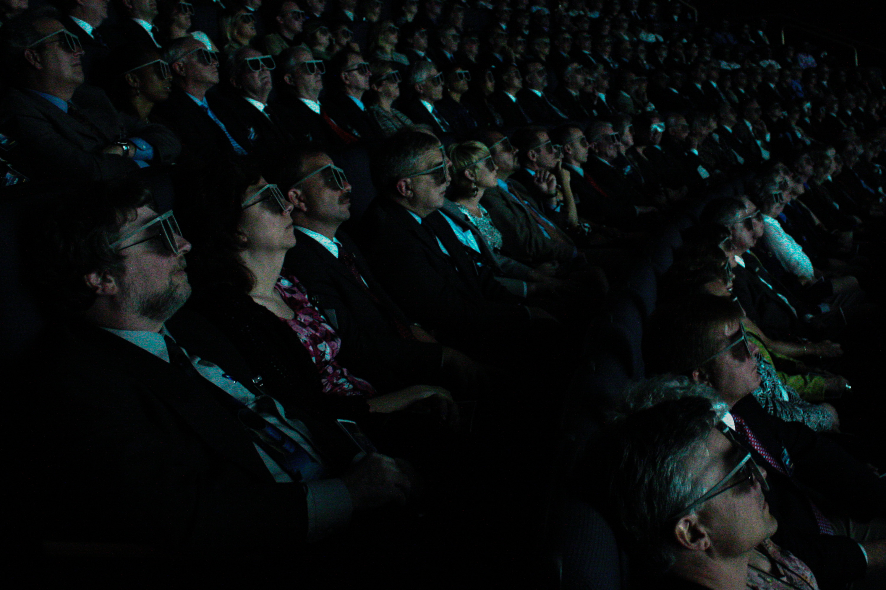 background image, a movie audience wearing 3-d glasses, all well dresssed and facing to the right